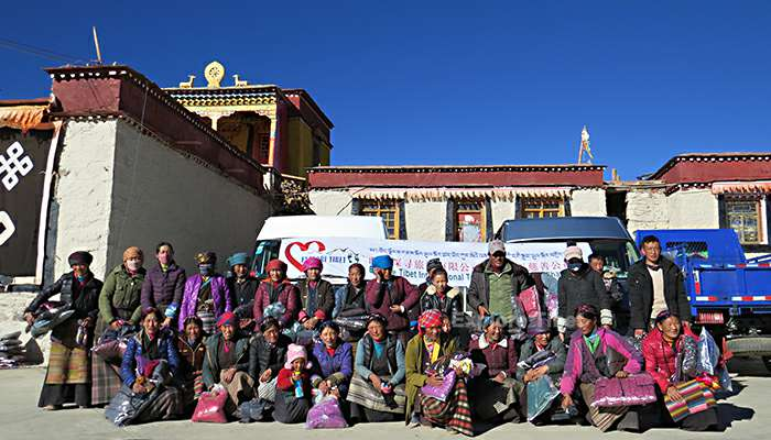 Explore Tibet staff with villagers in poor area